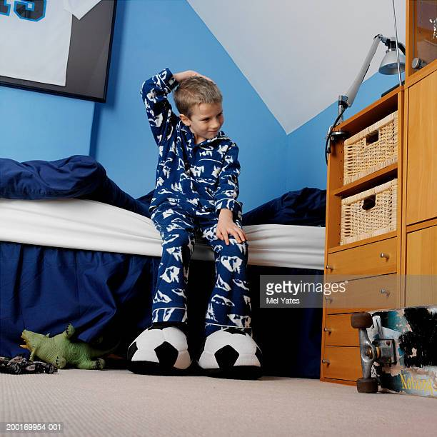 Boy (6-8) sitting on bed, holding hand to head, low angle view