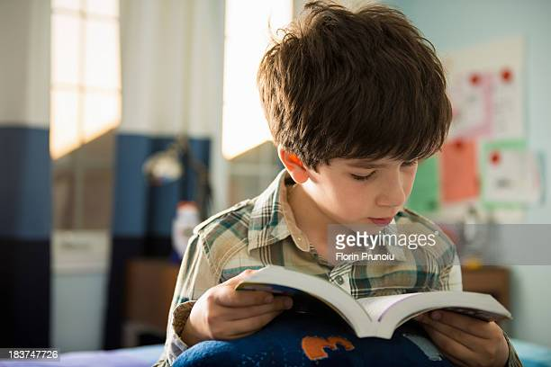 Boy sitting on bed reading book