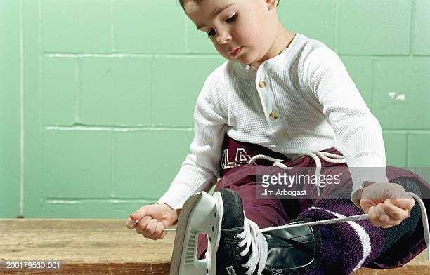 Boy (4-6) sitting on bench, tying hockey skates