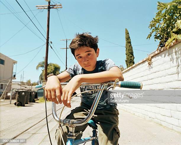 boy (13-15) sitting on bicycle, portrait - expression négative photos et images de collection