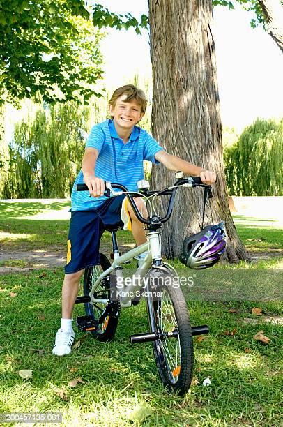 Boy (10-12) sitting on bike in park, smiling, portrait