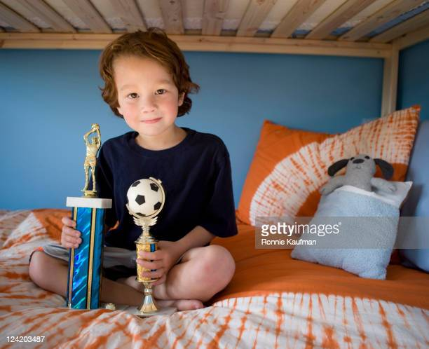 boy sitting on bunk bed with trophies