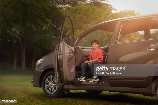 Boy sitting on car front seat in park