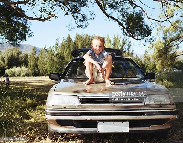 Boy (8-10) sitting on car, smiling, portrait