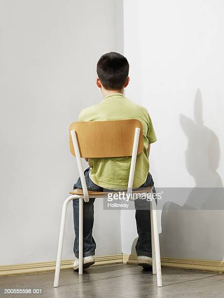 Boy (10-11) sitting on chair, rear view