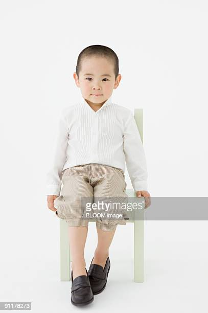 Boy sitting on chair, studio shot, portrait