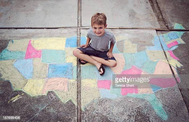 Boy sitting on chalk map of United States
