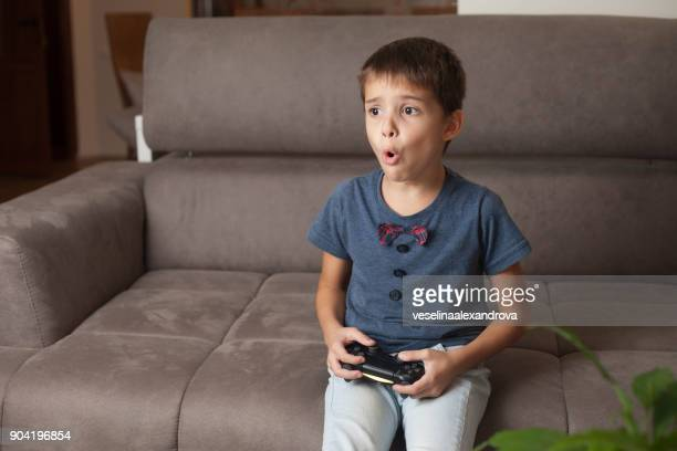 boy sitting on couch playing video games - losing virginity stock pictures, royalty-free photos & images