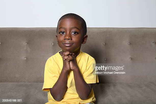 boy (4-5) sitting on couch with hands clasped - suplicar imagens e fotografias de stock