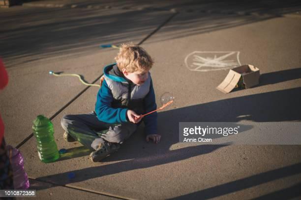 Boy sitting on driveway blowing bubbles