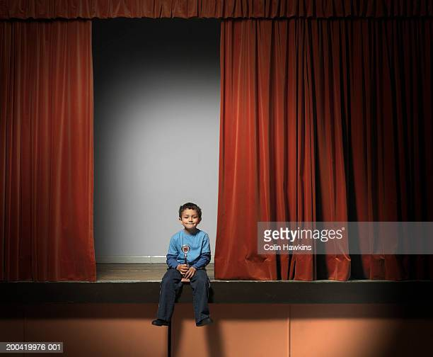 Boy (5-7) sitting on edge of stage holding trophy, portrait