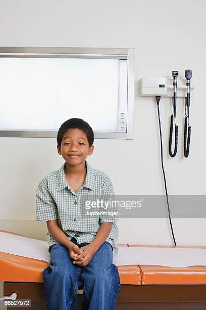 boy sitting on examining table - examination table stock pictures, royalty-free photos & images