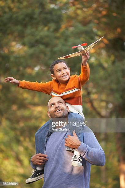 Boy sitting on father's shoulders and flying airplane