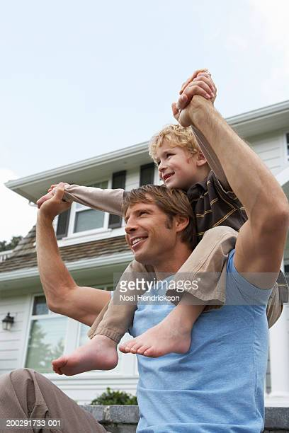 boy (5-7 years) sitting on father's shoulders outside house, smiling, close-up - 6 7 years stock pictures, royalty-free photos & images