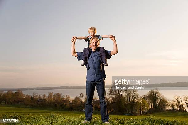 boy sitting on father's shoulders