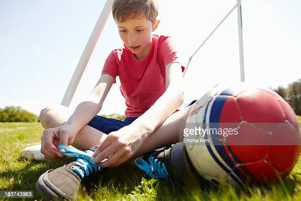 Boy sitting on field tying shoe lace