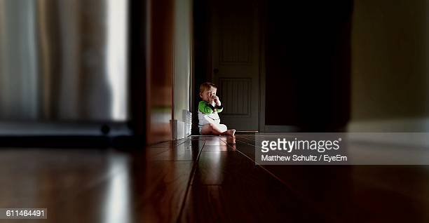 Boy Sitting On Floor At Home