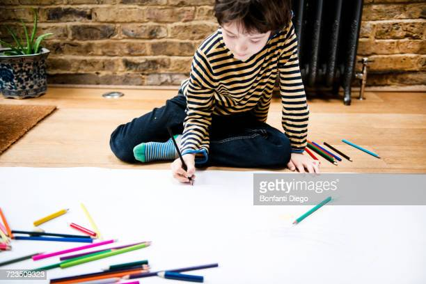 Boy sitting on floor drawing on large paper