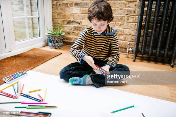 Boy sitting on floor drawing on long paper