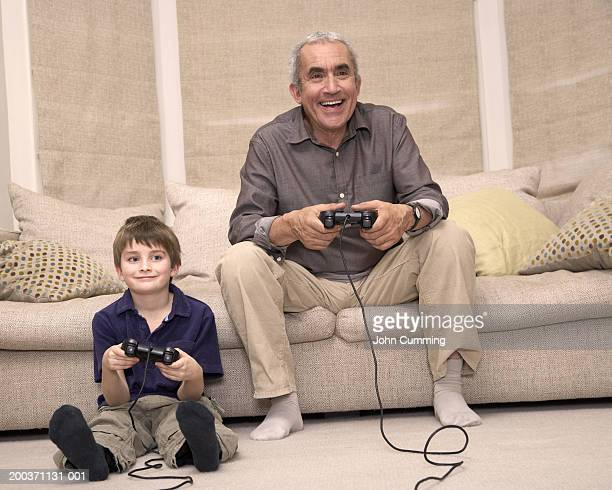 Boy (7-9) sitting on floor playing video game with grandfather