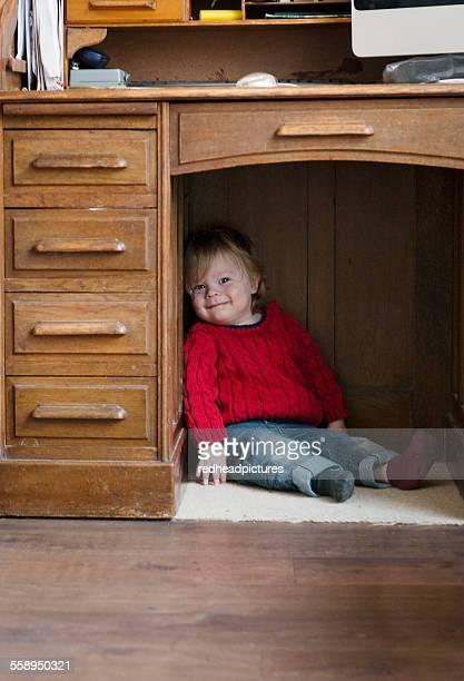 Boy sitting on floor under desk
