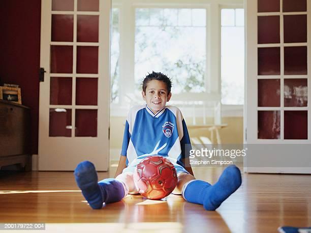 Boy (10-12) sitting on floor with soccer ball
