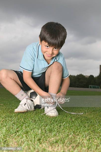 boy (7-9) sitting on football in field, tying shoelace, portrait - tying shoelace stock pictures, royalty-free photos & images