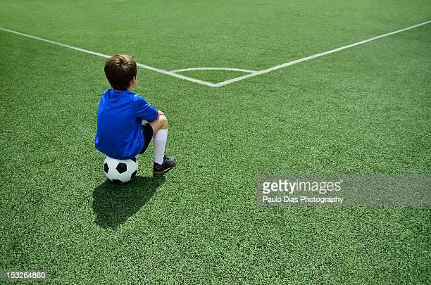 Boy sitting on football