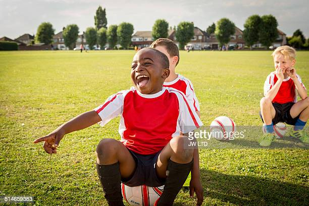 boy sitting on football pitch, laughing and pointi - sports uniform stock pictures, royalty-free photos & images