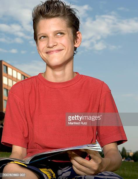 Boy (12-14) sitting on grass holding open magazine, smiling