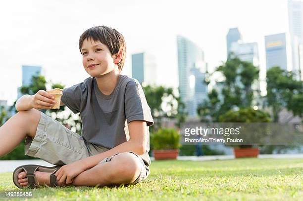 Boy sitting on grass in park, city skyline in background