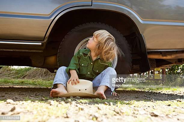 Petit garçon assis sur sol avec un chapeau de cow-Boy, de regarder en l'air