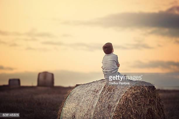 Boy sitting on hay bale at sunset