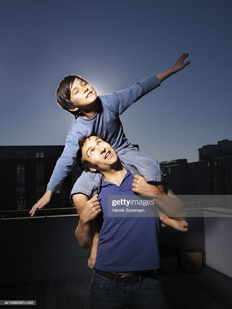 Boy (8-9) sitting on his father shoulders with extended arms : Foto stock