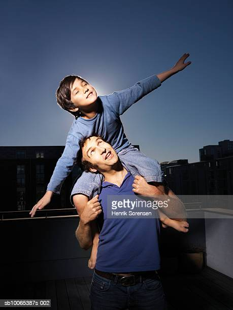 Boy (8-9) sitting on his father shoulders with extended arms