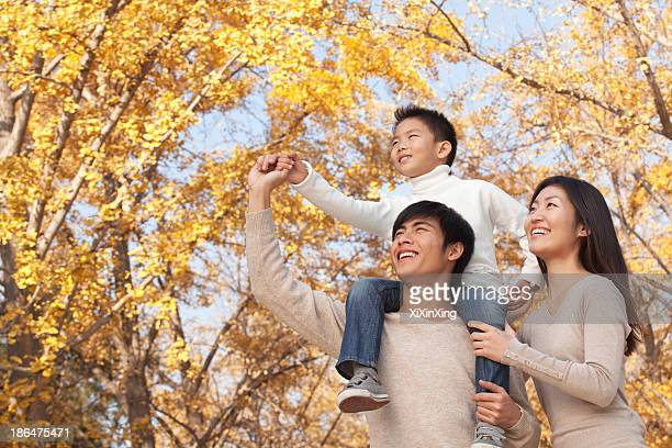 Boy sitting on his fathers shoulders in a park with family in Autumn