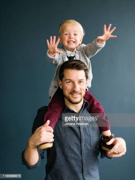 boy sitting on his father's shoulders - schulter stock-fotos und bilder