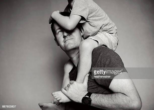 Boy sitting on his father's shoulders