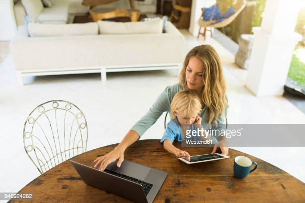 boy sitting on his mother's lap and looking at a tablet while his mother is working on a laptop - mom sits on sons lap stock pictures, royalty-free photos & images