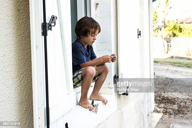Boy sitting on holiday apartment window ledge staring at bracelet, France