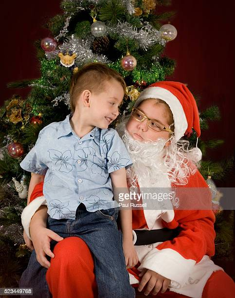 Boy Sitting on Lap of Boy Santa Claus