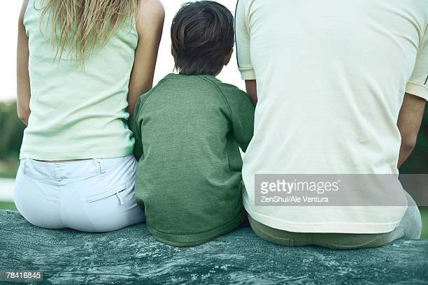 boy sitting on log between parents, rear view, cropped - femme entre deux hommes photos et images de collection