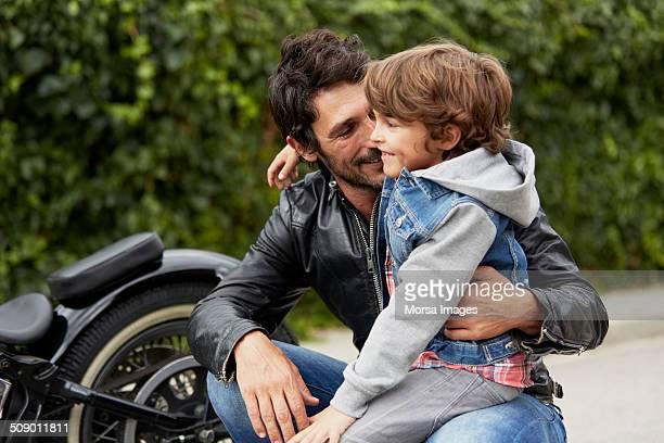 boy sitting on loving father's lap - familia con un hijo fotografías e imágenes de stock