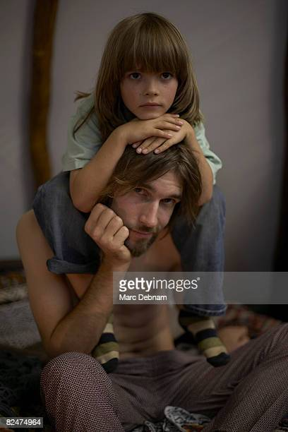 Boy sitting on man's shoulders, indoors