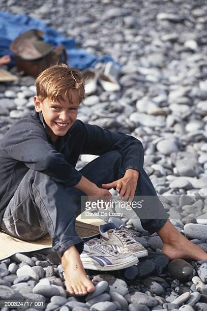 Boy (10-11) sitting on mat at pebble beach