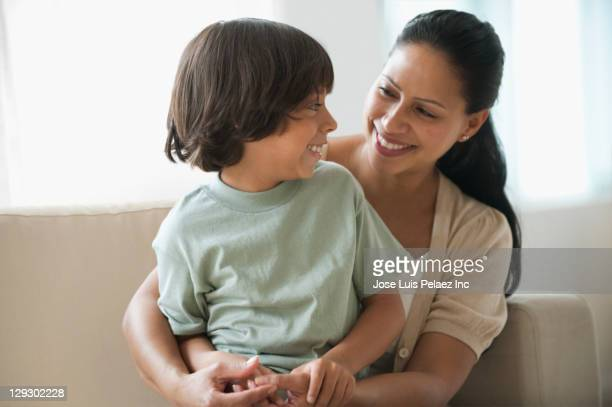 boy sitting on mother's lap - mom sits on sons lap stock pictures, royalty-free photos & images