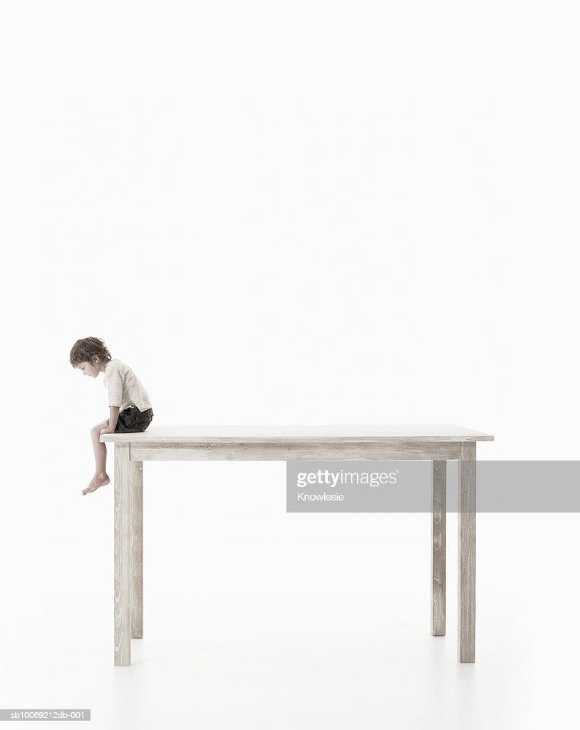 Boy (4-5 years) sitting on oversized table, studio shot, side view : Stockfoto