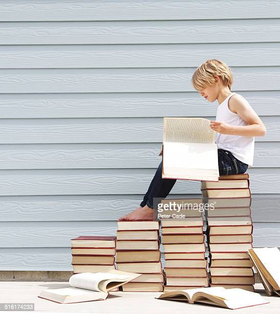 boy sitting on pile of books . Boy reading book.
