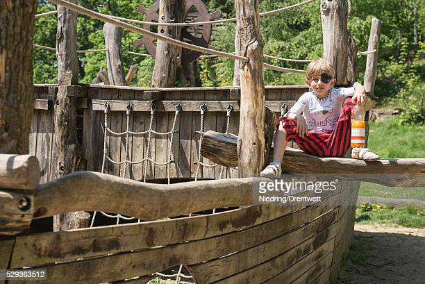 Boy sitting on pirate play ship in adventure playground, Bavaria, Germany