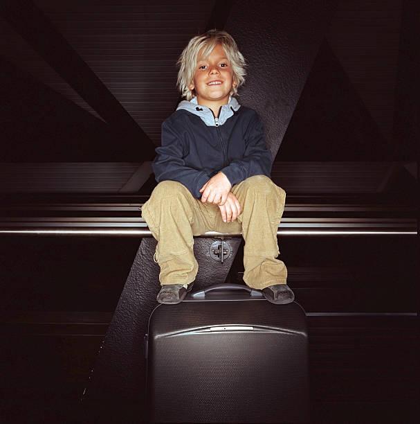Boy (6-8) sitting on rail with feet on suitcase, portrait